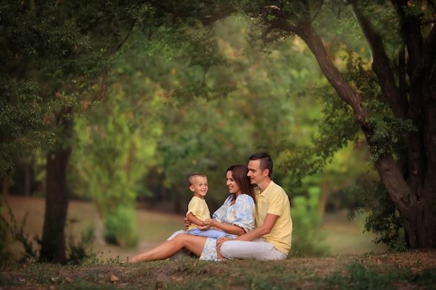 Szczęśliwa rodzina z małym dzieckiem na spacerze w parku