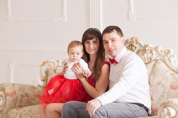 Szczęśliwa rodzina z małym dzieckiem pozuje w rodzinnym stylu mody