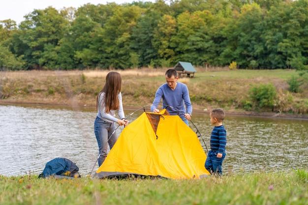 Szczęśliwa rodzina z małym synem rozbili namiot kempingowy. szczęśliwe dzieciństwo, wyjazd na kemping z rodzicami. dziecko pomaga rozłożyć namiot