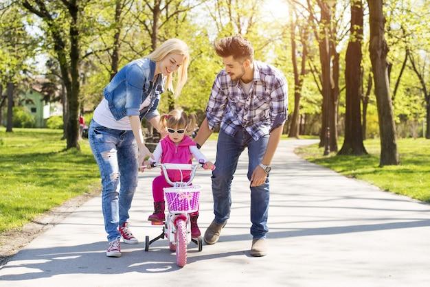 Szczęśliwa rodzina z młodymi rodzicami, ucząc córkę, jak jeździć na rowerze