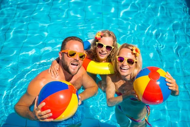 Szczęśliwa rodzina z okularami przeciwsłonecznymi i kwiatami na włosach z kolorowymi dmuchańcami w basenie