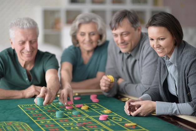 Szczęśliwa rodzina z parą seniorów grającą z żetonami w kasynie