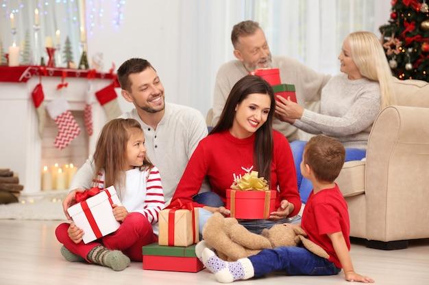 Szczęśliwa rodzina z prezentami świątecznymi w domu