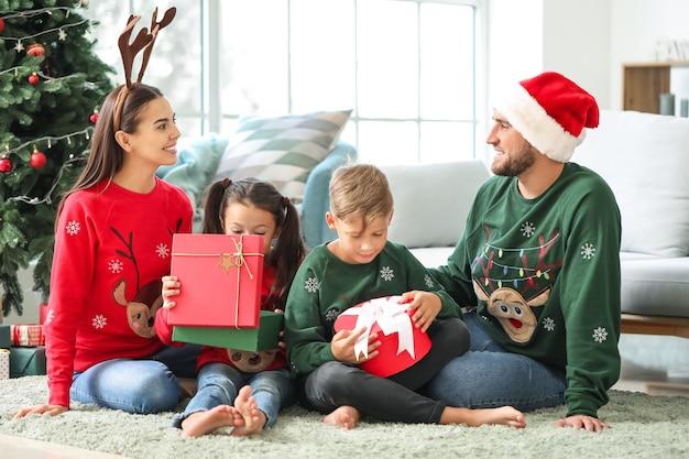 Szczęśliwa rodzina z prezentami w domu w wigilię bożego narodzenia