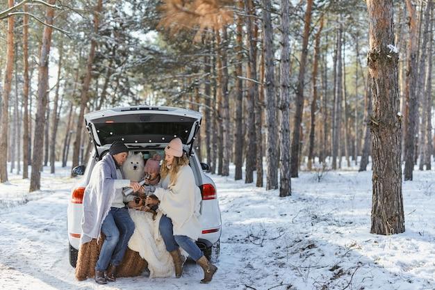 Szczęśliwa rodzina z psem na wakacjach podczas ferii zimowych w pobliżu drogi. ubrani w ciepłe ubrania siedząc na bagażniku samochodu i pijąc herbatę z termosu. miejsce na tekst. ferie zimowe