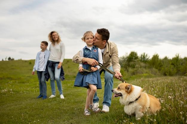 Szczęśliwa rodzina z psem na zewnątrz pełnego ujęcia