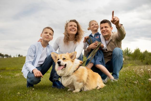 Szczęśliwa rodzina z psem na zewnątrz pełny strzał