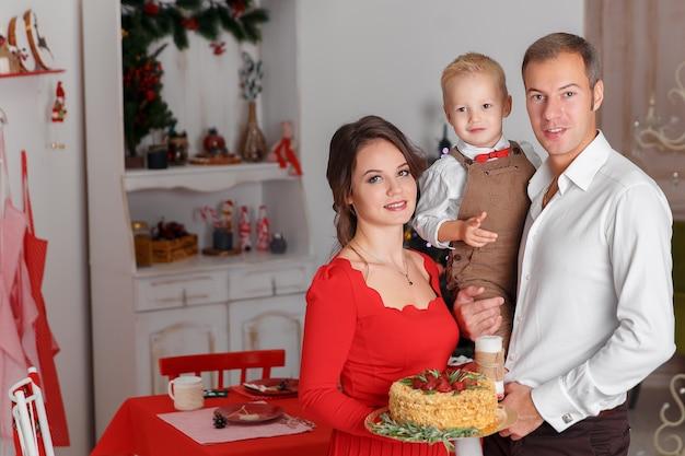 Szczęśliwa rodzina z pysznym tortem na tle kuchni. święto nowego roku i zabawa.