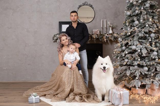 Szczęśliwa rodzina z samoyed psem świętującym boże narodzenie w domu w pobliżu udekorowanej choinki