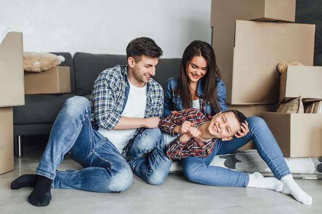 Szczęśliwa rodzina z tekturowymi pudłami bawiąca się z synem