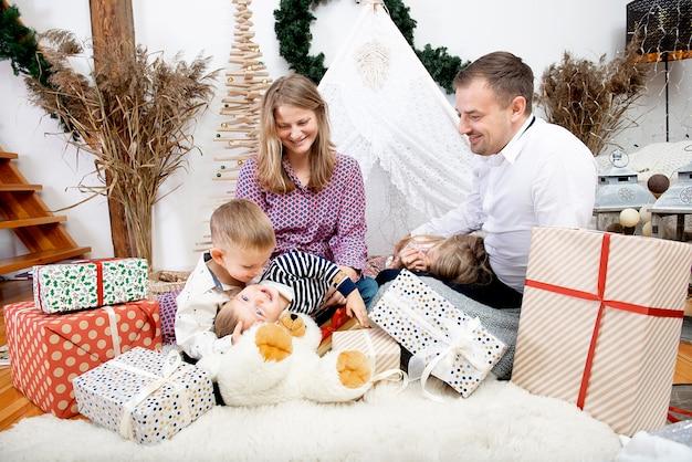 Szczęśliwa rodzina z trójką dzieci obchody bożego narodzenia na zdobionym tle w domu. szczęśliwe dzieciństwo, rodzicielstwo, szczęśliwe wakacje i koncepcja rodziny.