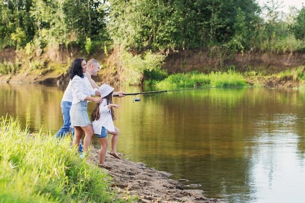 Szczęśliwa rodzina z wędką na rzece latem