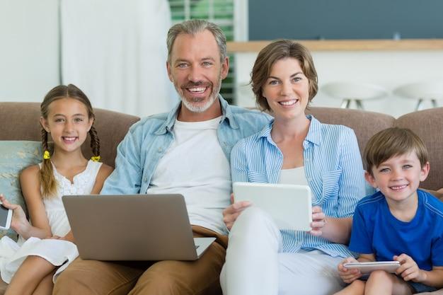 Szczęśliwa rodzina za pomocą telefonu komórkowego, cyfrowego tabletu i laptopa w salonie