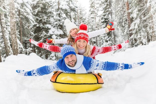 Szczęśliwa rodzina zabawy na świeżym powietrzu. dziecko, matka i ojciec bawią się w okresie zimowym. koncepcja aktywnego zdrowego stylu życia