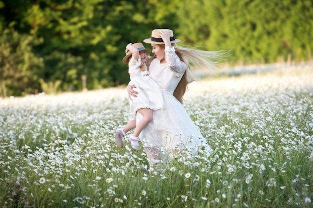 Szczęśliwa rodzina zabawy na świeżym powietrzu. portret szczęśliwa rodzina w wsi. szczęśliwi ludzie na zewnątrz. czteroosobowa rodzina w polu rumianku.