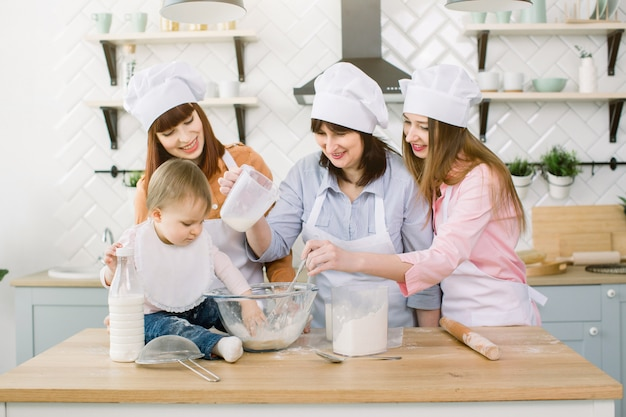 Szczęśliwa rodzina zabawy w kuchni. babcia i jej córki oraz mała dziewczynka wyrabiające ciasto razem w kuchni w domu. szczęśliwego dnia matki, rodzinne gotowanie