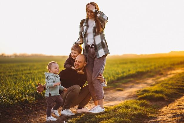 Szczęśliwa rodzina zabawy w polu na zachód słońca