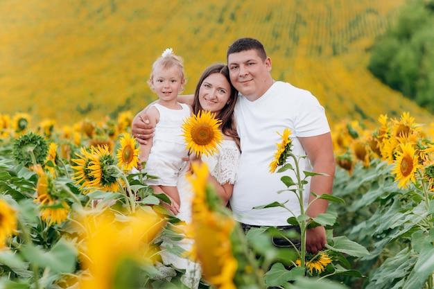 Szczęśliwa rodzina zabawy w polu słoneczników. macierzysty mienie jej córka i słonecznik w ręce. pojęcie wakacji letnich. dzień matki, ojca, dziecka. rodzina wspólnie spędza czas