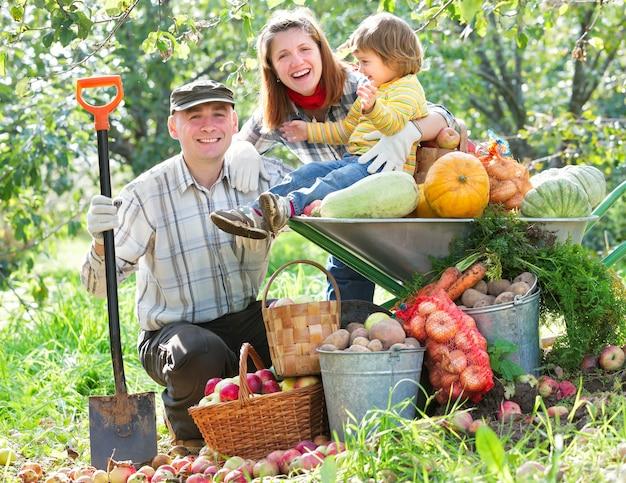 Szczęśliwa rodzina ze zbiorami owoców i warzyw