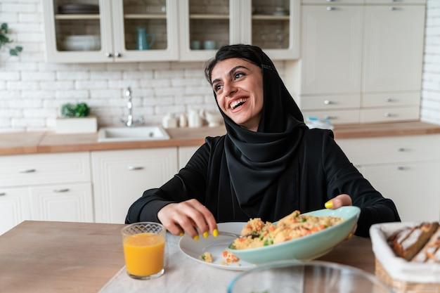 Szczęśliwa rodzina ze zjednoczonych emiratów arabskich jedząca razem i świętująca święta narodowe