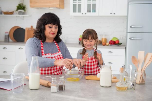 Szczęśliwa rodzinna babcia i mała wnuczka w fartuchach kucharskich gotujących razem w kuchni