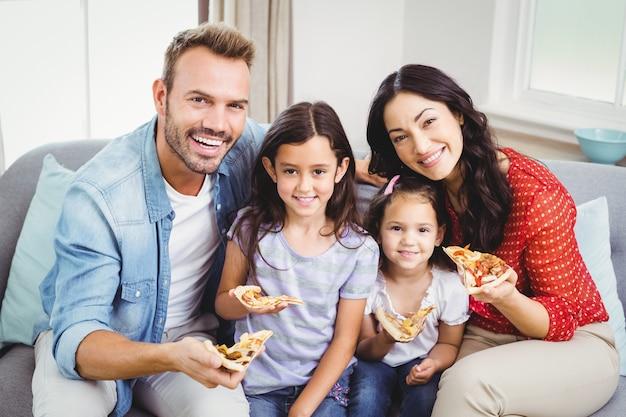 Szczęśliwa rodzinna łasowanie pizza podczas gdy siedzący na kanapie