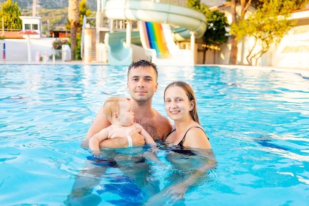Szczęśliwa rodzinna mama, tata i córeczka pływają w basenie ze zjeżdżalniami i bawią się na wakacjach