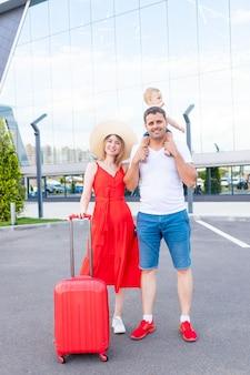 Szczęśliwa rodzinna mama, tata i dziecko na lotnisku z czerwoną walizką jedzie na wycieczkę lub wakacje