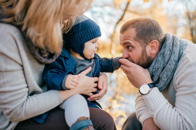 Szczęśliwa rodzinna para z ich małym dzieckiem w jesień parku w słonecznym dniu
