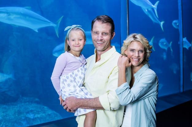 Szczęśliwa rodzinna patrzeje kamera obok rybiego zbiornika