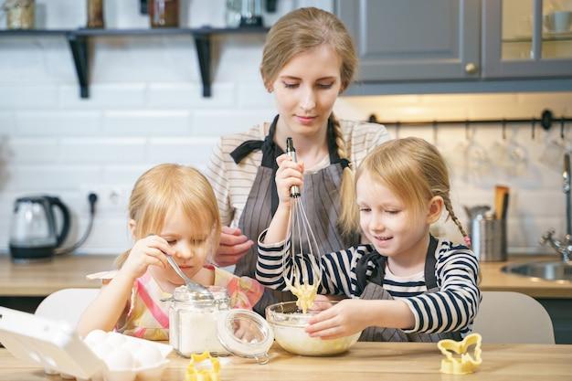 Szczęśliwa rodzinna potomstwo matka i dwie małe córki robi ciastu