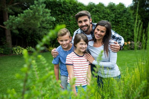 Szczęśliwa rodzinna pozycja na trawie w parku na słonecznym dniu