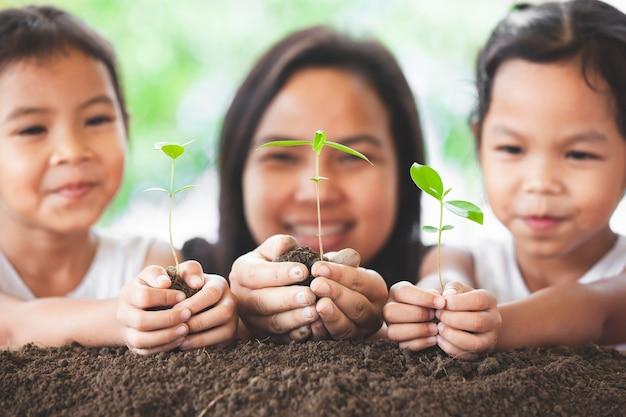 Szczęśliwa rodziny matka i córka ma zabawę trzymać młodego drzewa w rękach dla zasadzać