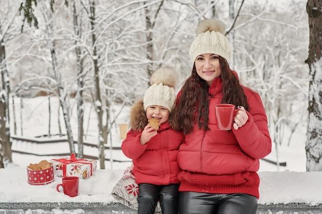 Szczęśliwa rodziny matka i dziecko córka na zimie chodzimy outdoors pić herbaty. szczęśliwa rodzina matka i dziecko małe dziecko bawi się w zimowe święta bożego narodzenia. święta rodzina w winter park.