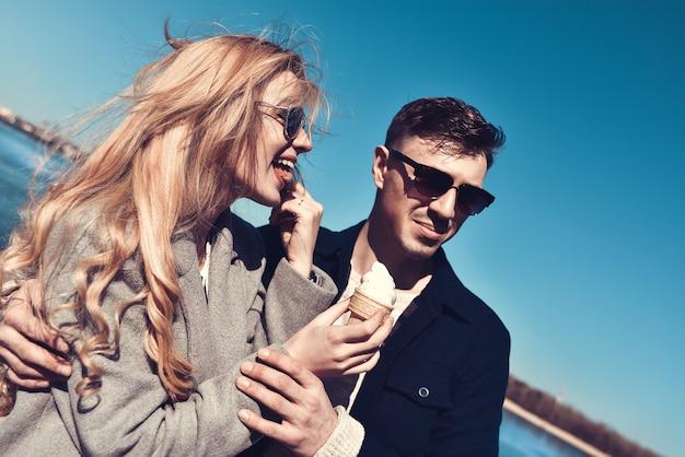 Szczęśliwa romantyczna para kaukaski w okulary przeciwsłoneczne. zabawna dziewczyna je lody