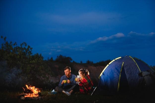 Szczęśliwa romantyczna para podróżnych odpoczywa przy ognisku w pobliżu świecącego namiotu turystycznego pod niesamowitym nocnym niebem
