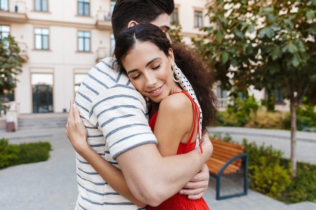 Szczęśliwa romantyczna para w zwykłych ubraniach uśmiechnięta i przytulająca się podczas spaceru ulicą miasta