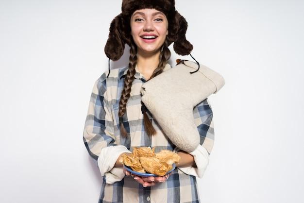 Szczęśliwa rosjanka w kapeluszu z futrzanym kapeluszem świętuje zapusty jedząc naleśniki