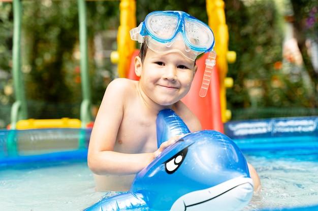 Szczęśliwa roześmiana berbeć chłopiec ma zabawę w pływackim basenie