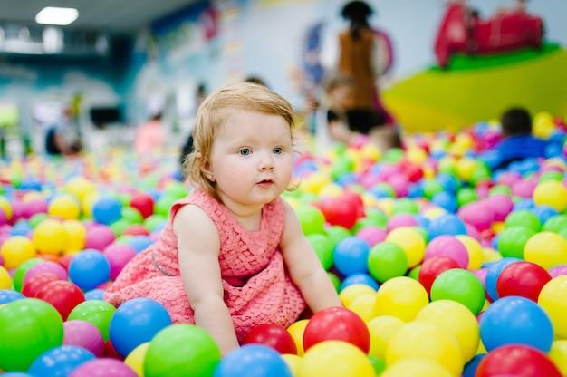 Szczęśliwa roześmiana dziewczyna bawi się zabawkami, kolorowe kulki na placu zabaw, basen z piłeczkami, suchy basen. małe słodkie dziecko zabawy w piłkę na przyjęcie urodzinowe w parku rozrywki dla dzieci i centrum zabaw kryty.