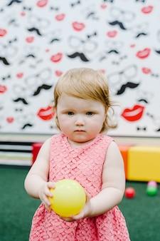 Szczęśliwa roześmiana dziewczyna bawi się zabawkami, kolorowymi kulkami na placu zabaw w sali gier. małe słodkie zabawy dziecko na przyjęcie urodzinowe w parku rozrywki dla dzieci i centrum zabaw kryty.