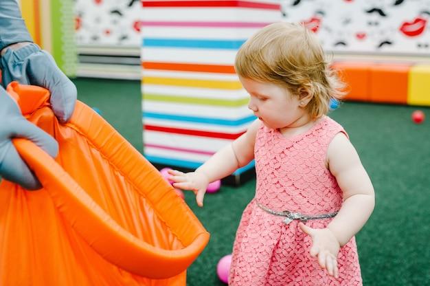 Szczęśliwa Roześmiana Dziewczyna Bawi Się Zabawkami, Kolorowymi Kulkami Na Placu Zabaw W Sali Gier. Małe Słodkie Zabawy Dziecko Na Przyjęcie Urodzinowe W Parku Rozrywki Dla Dzieci I Centrum Zabaw Kryty. Premium Zdjęcia