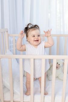 Szczęśliwa roześmiana dziewczynka w łóżeczku w przedszkolu w białym body