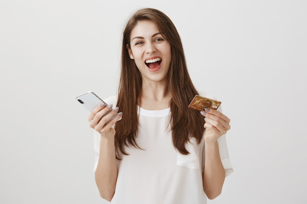Szczęśliwa roześmiana kobieta zamawia online za pośrednictwem aplikacji na smartfona, trzymając kartę kredytową i telefon komórkowy
