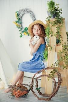 Szczęśliwa roześmiana mała dziewczynka bawić się z dziecko królikiem
