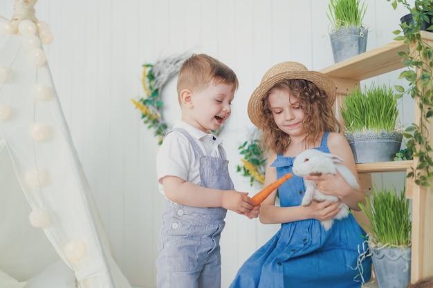 Szczęśliwa roześmiana mała dziewczynka i chłopiec bawić się z dziecko królikiem