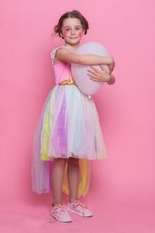Szczęśliwa roześmiana mała dziewczynka z długimi włosami tańczy na różowym tle