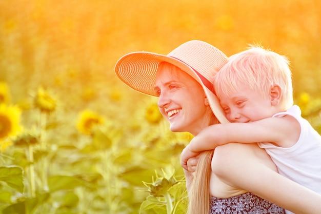 Szczęśliwa roześmiana matka daje berbecia syna piggyback przejażdżce