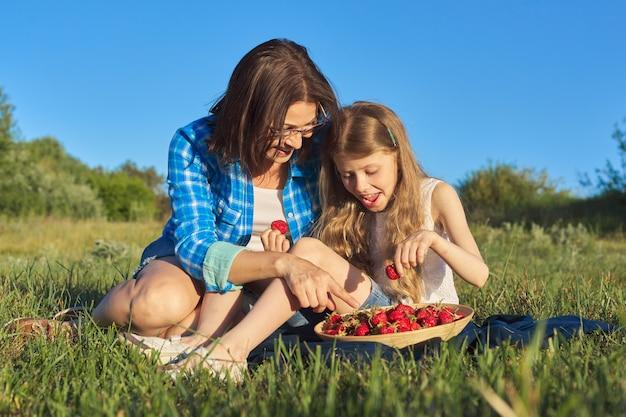 Szczęśliwa roześmiana matka i córka dziecka razem na zewnątrz, siedząc na zielonej trawie, piknik z miską świeżych truskawek. dzień matki, majowa natura