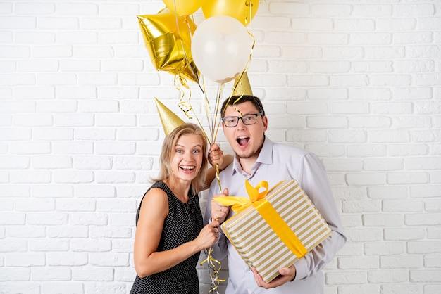 Szczęśliwa roześmiana para obchodzi urodziny trzymając złote balony